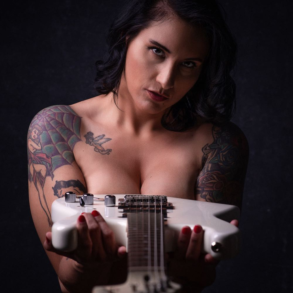 Semi nude photo of a woman holding a guitar