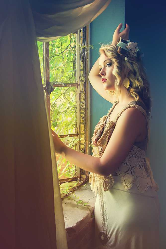 Glamour photo of a woman looking out a window