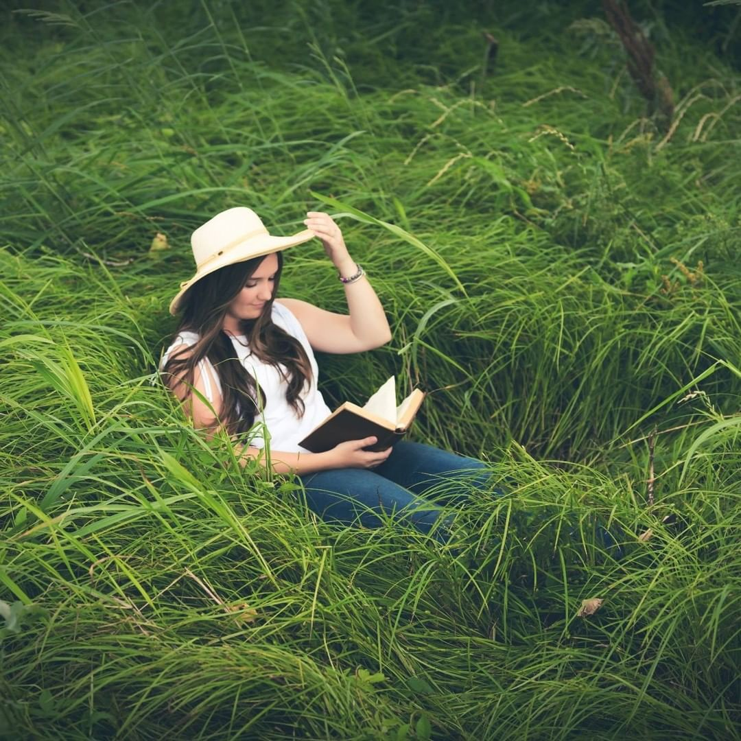 Girl reading a book in tall grass