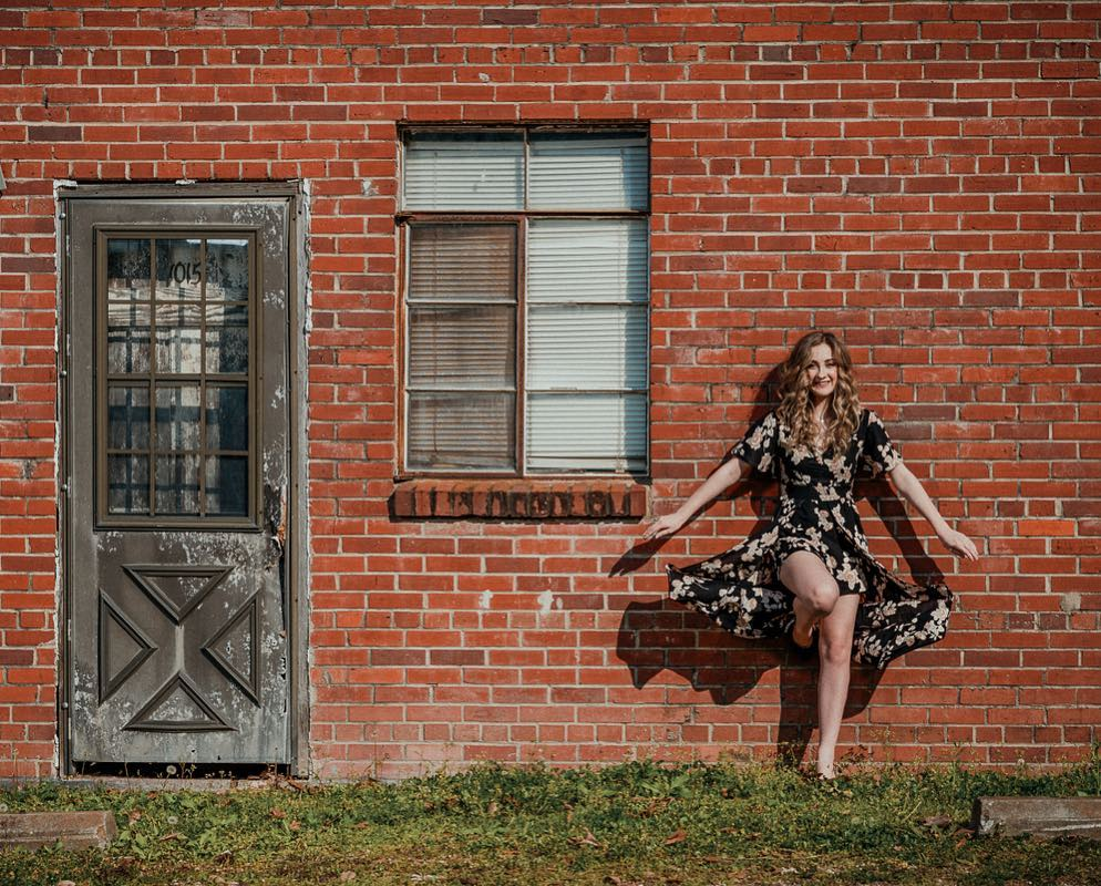 Glamour photo of a girl against a brick wall