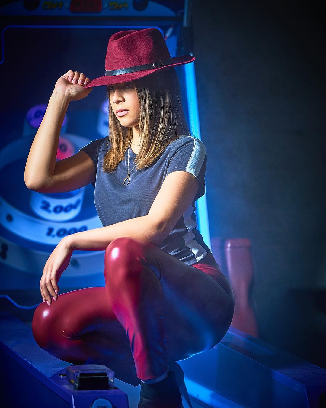 Neon glamour photo of a woman in red leather pants and hat