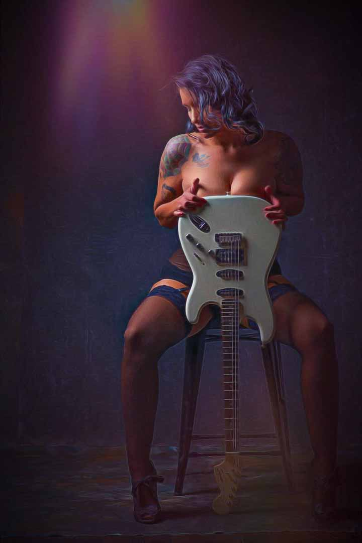 Road House style glamour / boudoir shot of a woman nude with a guitar in front of her