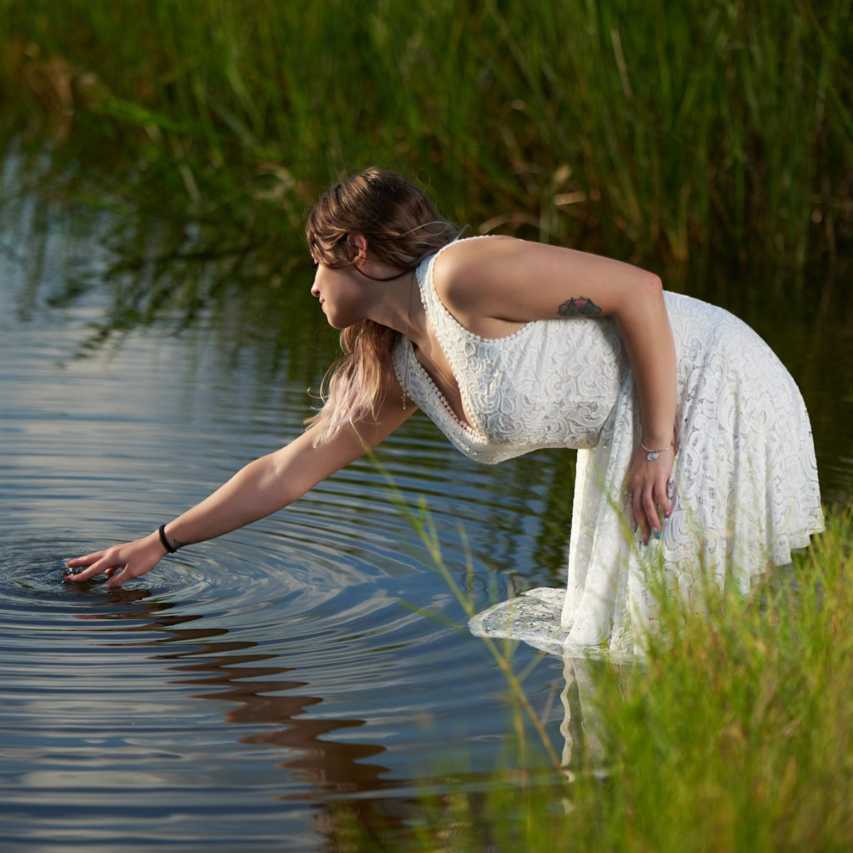 Girl touching the surface of a pond